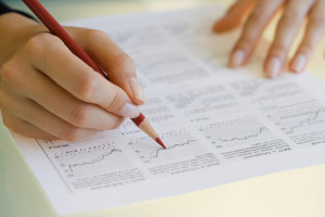 Woman writing on financial charts